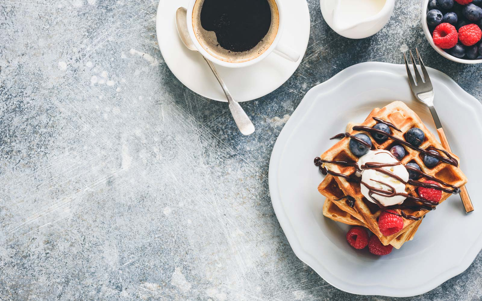 Belgian waffles with ice cream, berries and cup of coffee