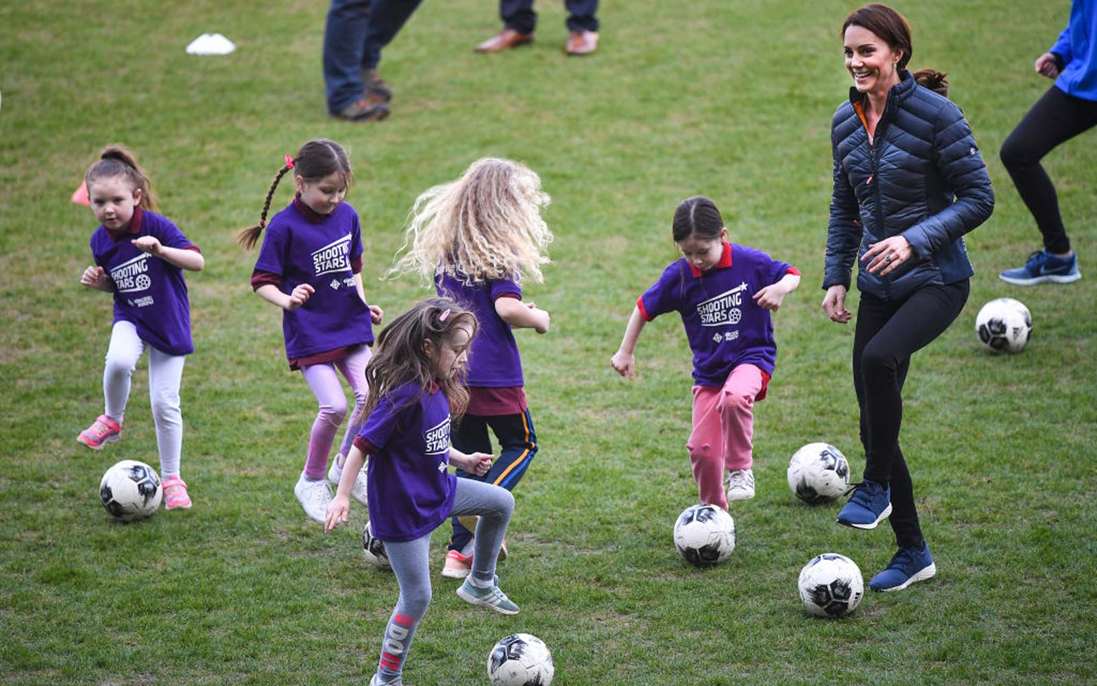 Catherine, Duchess of Cambridge plays some football with young girls as she visits Windsor Park Stadium