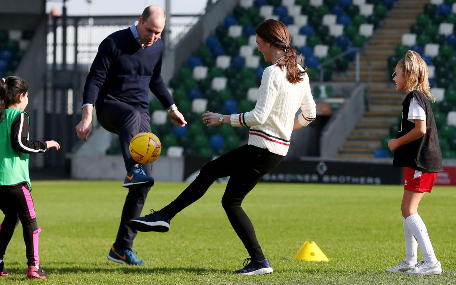 Prince William Duke of Cambridge and Catherine, Duchess of Cambridge, play football during a visit the National Stadium in Belfast