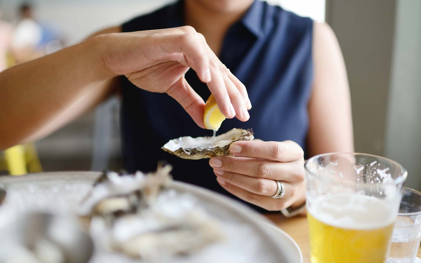 Woman squeezing lemon onto a raw oyster