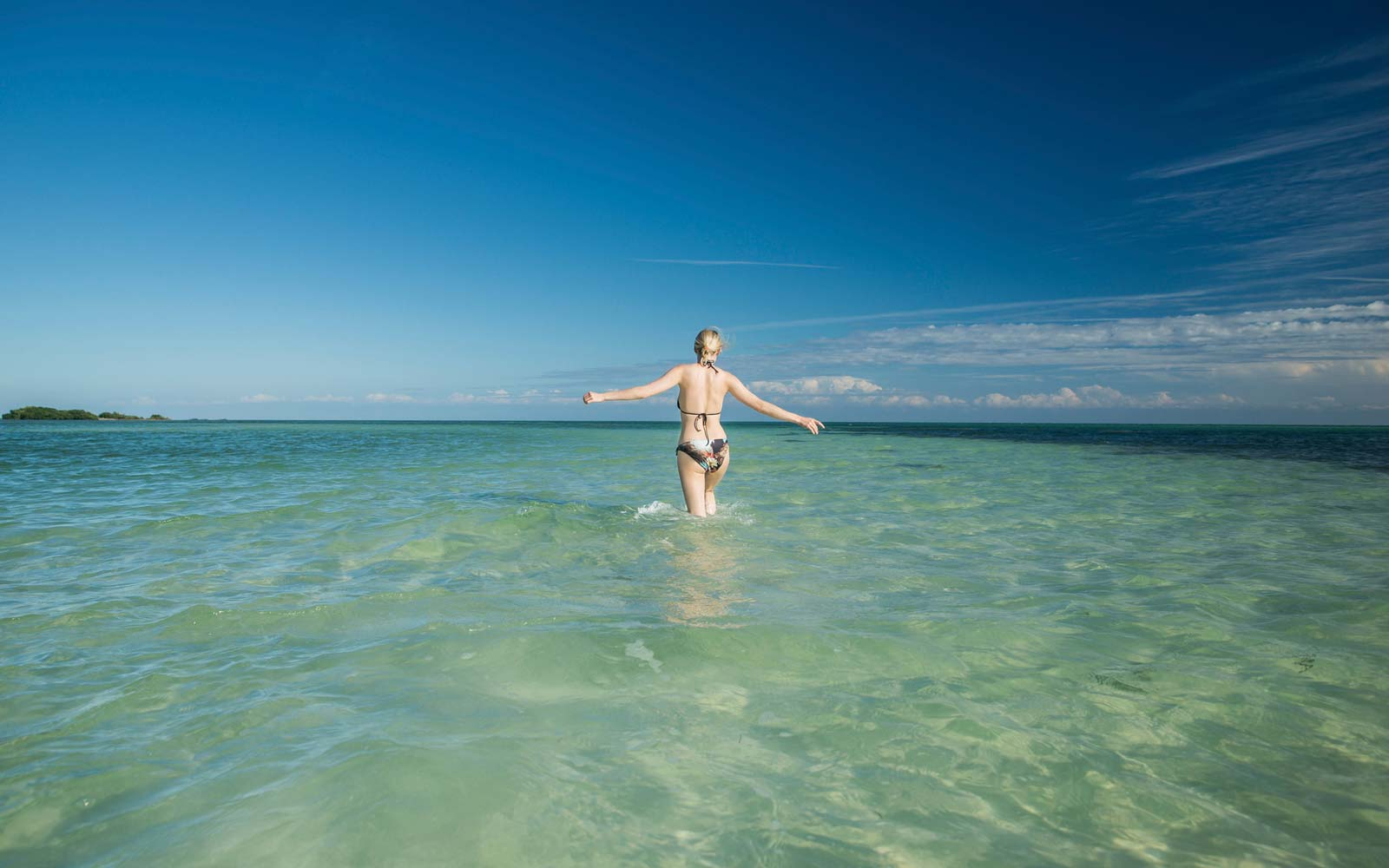 USA, Florida, Key West, Bahia Honda State Park, back view of woman wading into the sea