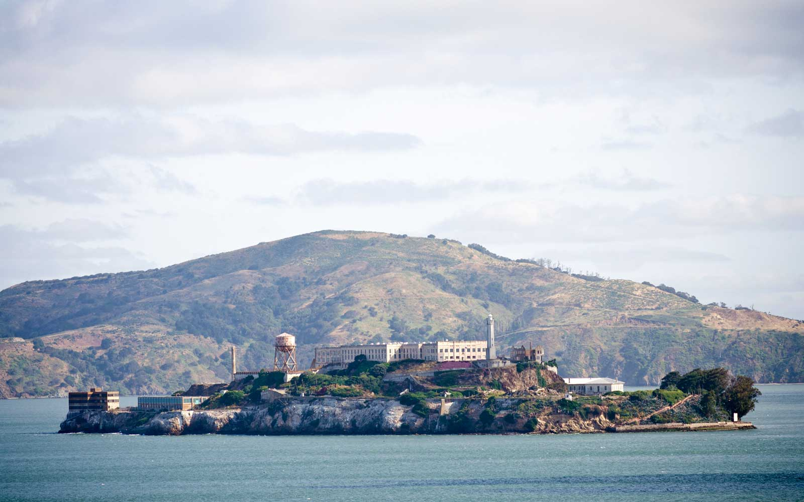 Alcatraz Island in San Francisco Bay with Angel Island State Park in the background.