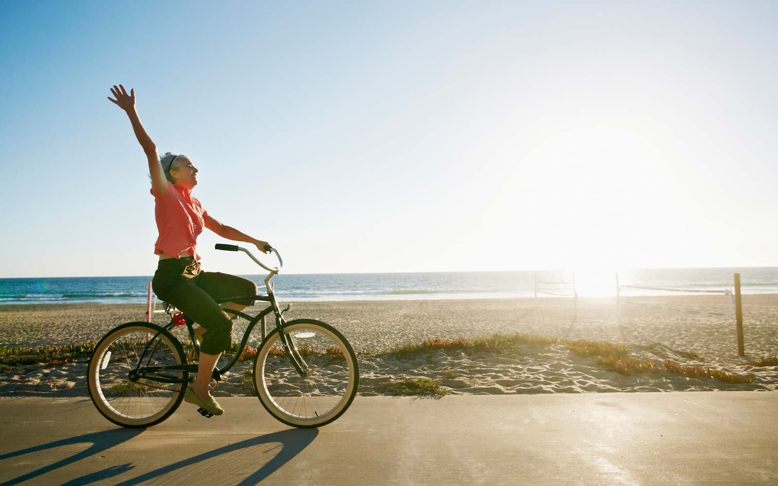 Caucasian woman riding bicycle near beach