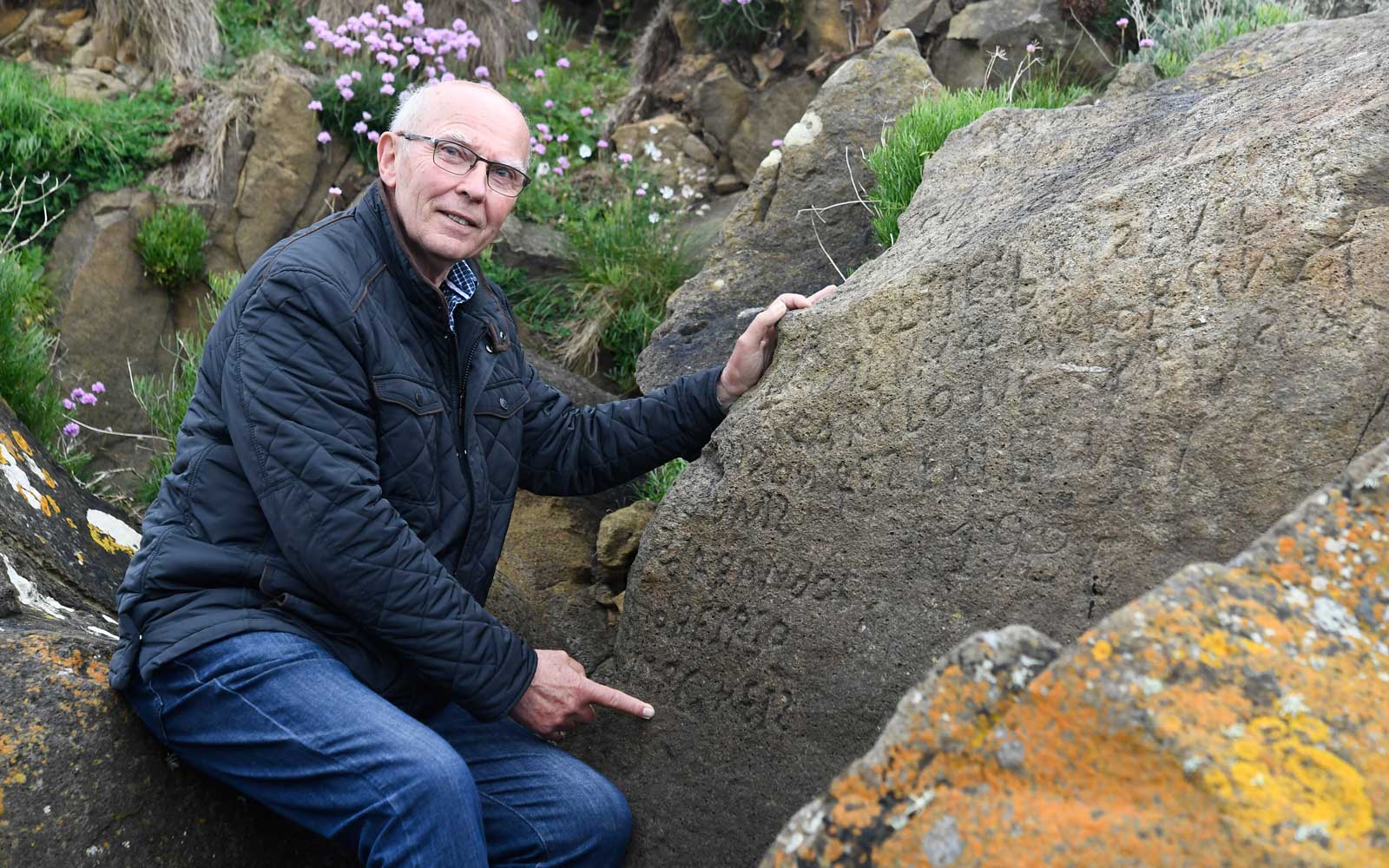 French local councillor in charge of small heritage Michel Paugam poses on May 7, 2019 as he shows inscriptions composing indecipherable words on a rock in the Brittany village of Plougastel-Daoulas.