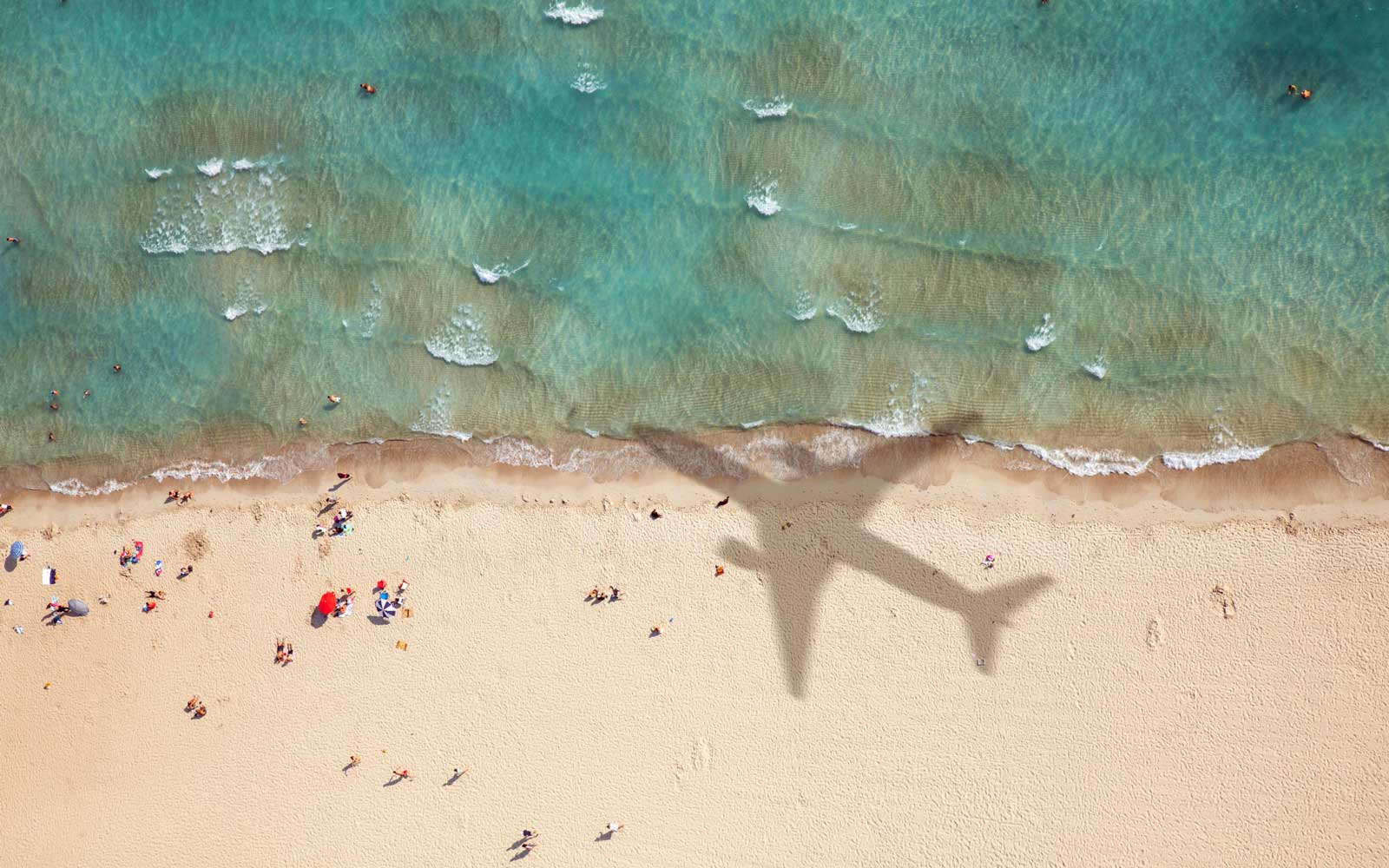 Plane flying over beach