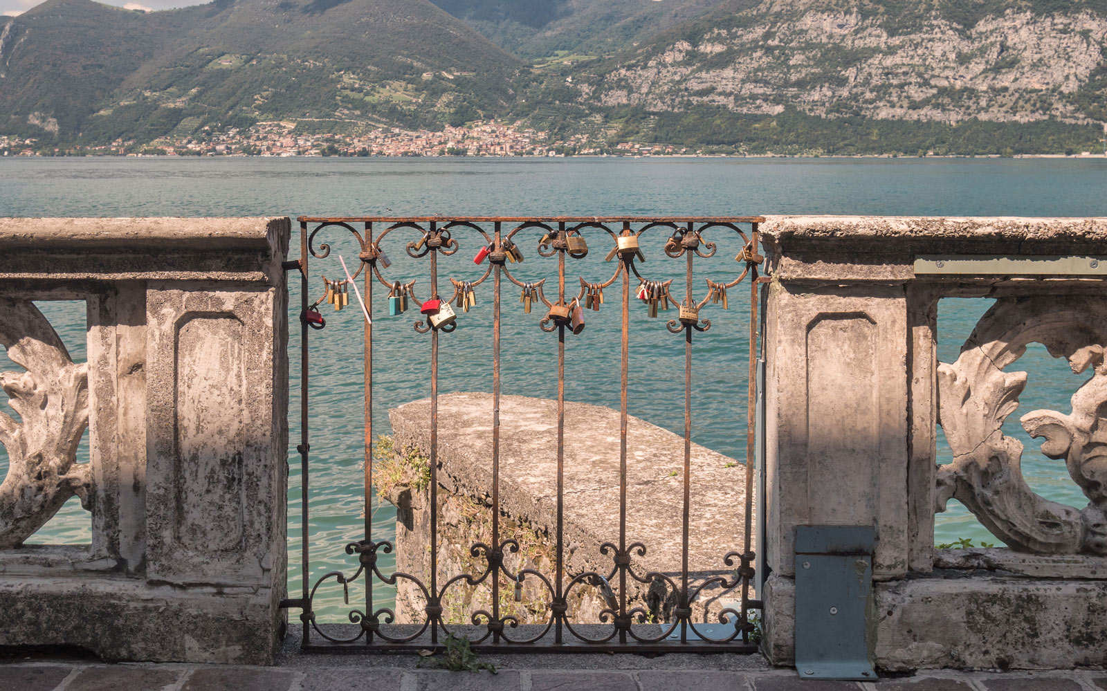 A gate with love locks overlooking Lake Iseo