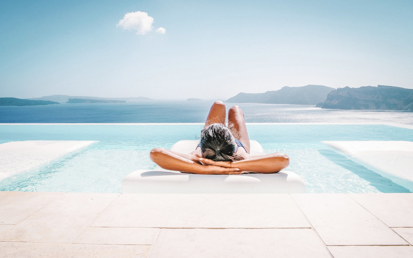 Person relaxing by water on vacation