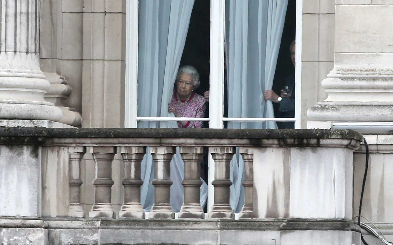 Queen Elizabeth II looking out of the window at Buckingham Palace