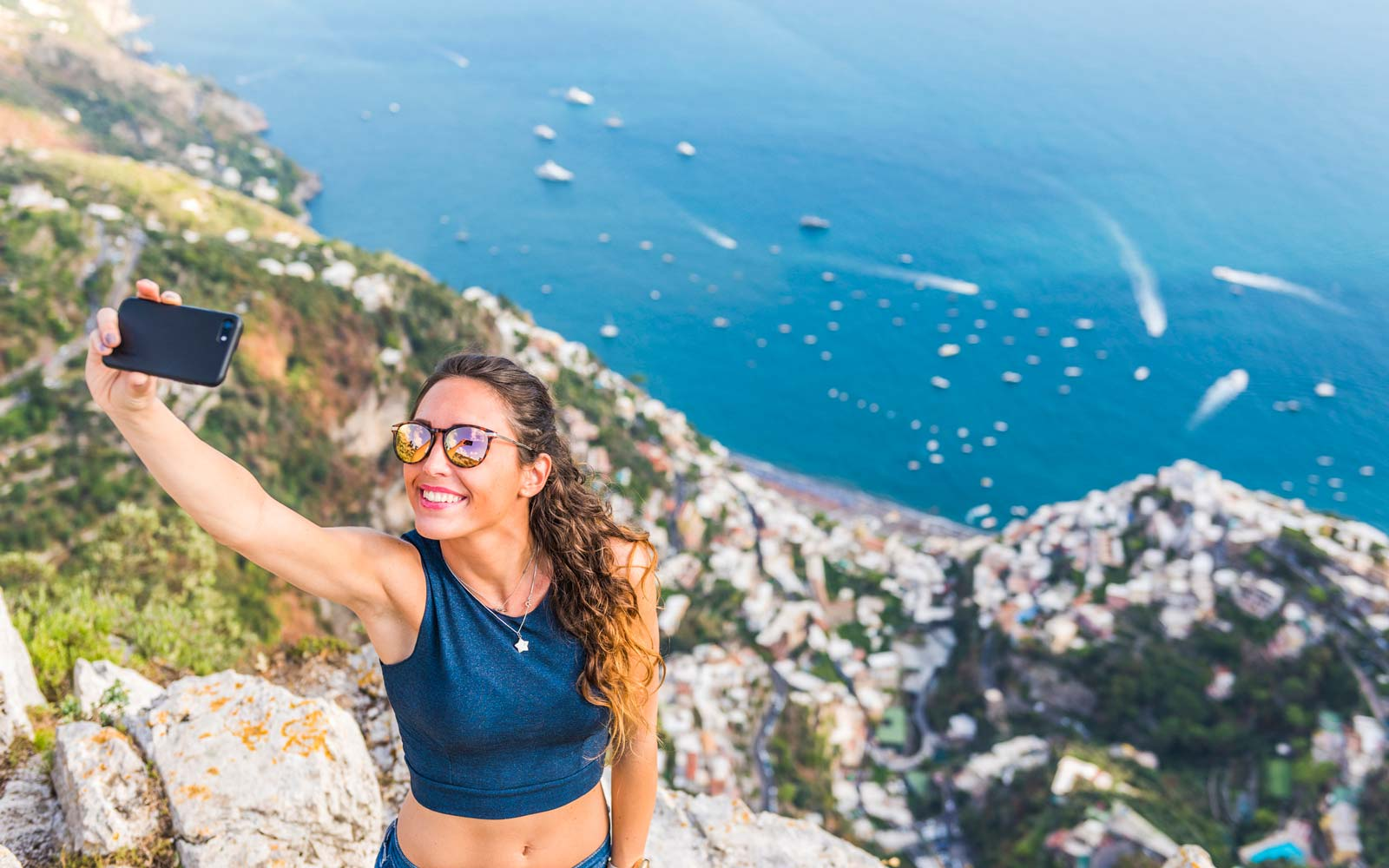 A young woman is taking a selfie. Positano village in the background
