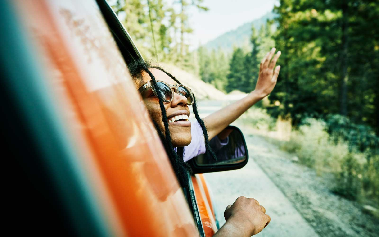 Woman looks out of car window while traveling