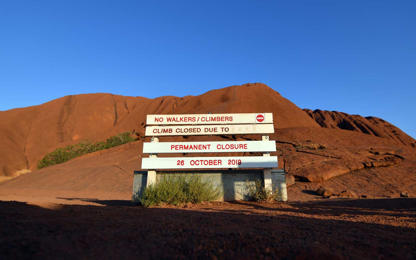 New signage marking a permanent ban on climbing Uluru, also known as Ayers Rock, is seen at the base of the monolith at Uluru-Kata Tjuta National Park in Australia's Northern Territory on October 25, 2019