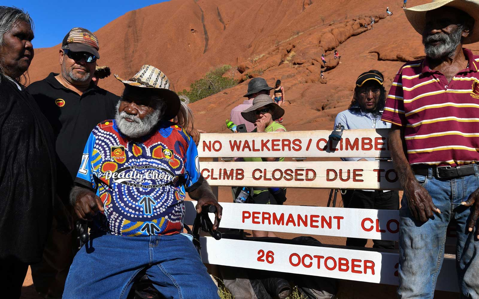 Aboriginal elders stand beside new signage at the base of Uluru