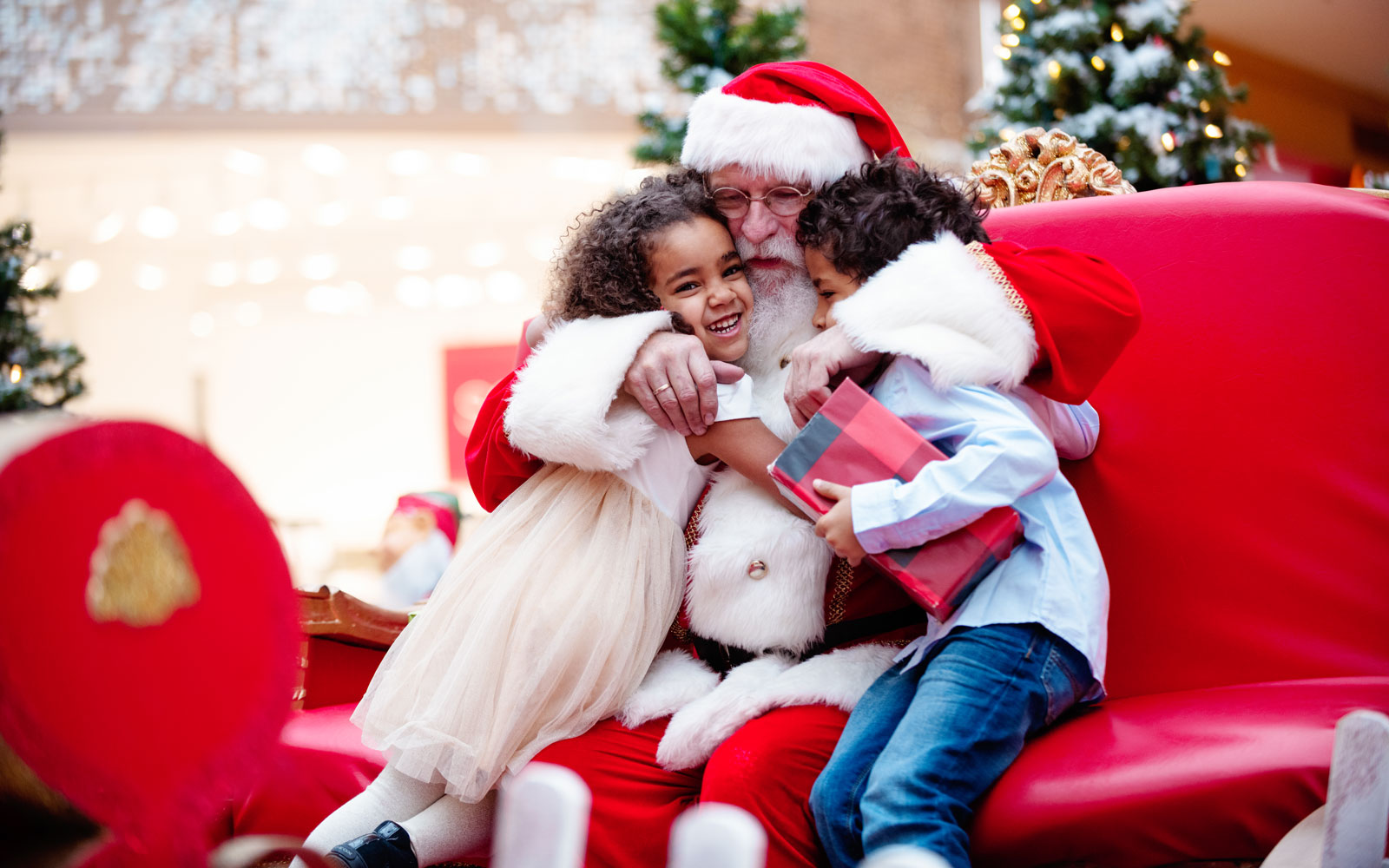 Two kids hugging Santa Claus