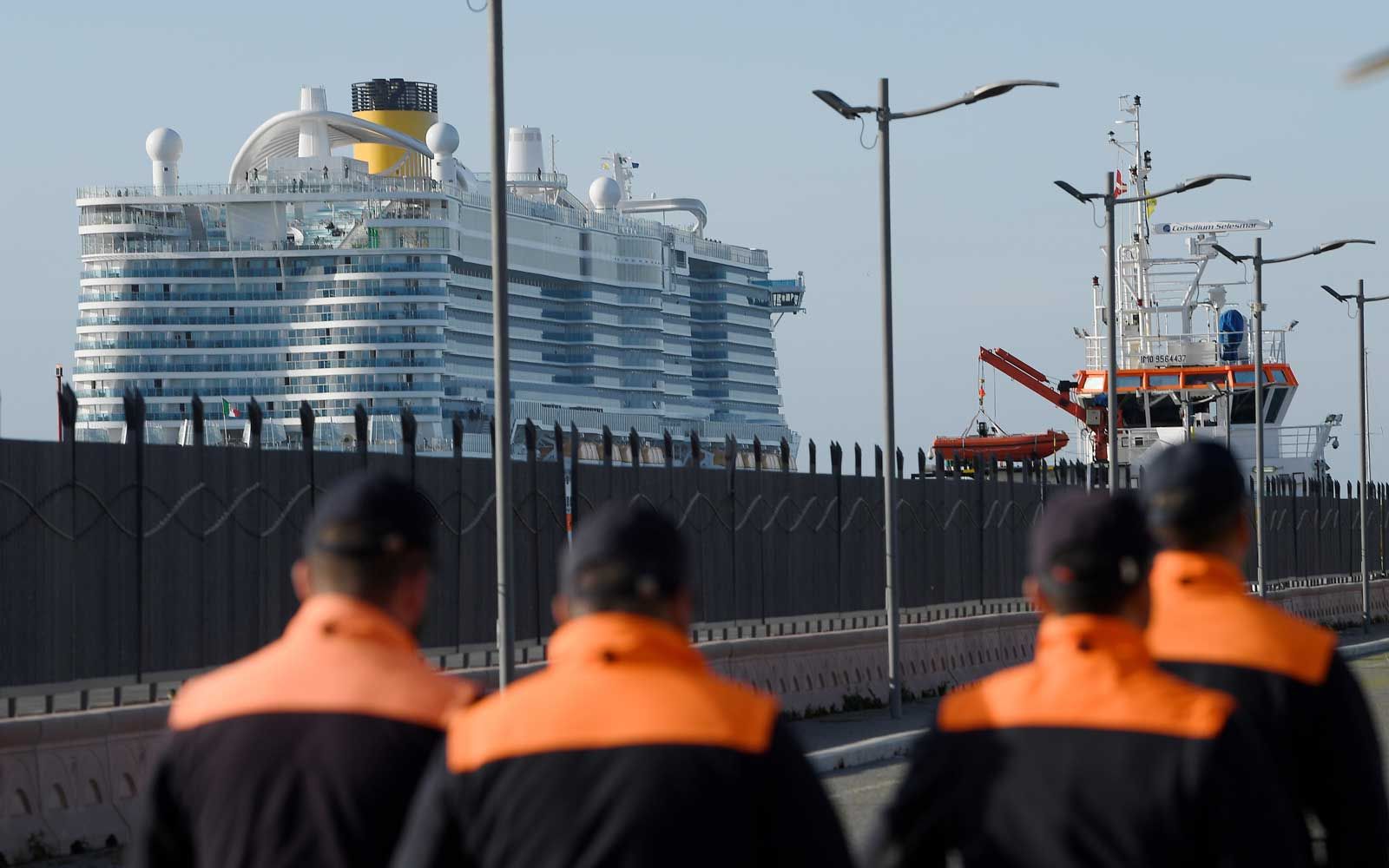 Coastguard members walk past the Costa Smeralda cruise ship docked in the Civitavecchia port 70km north of Rome on January 30, 2020