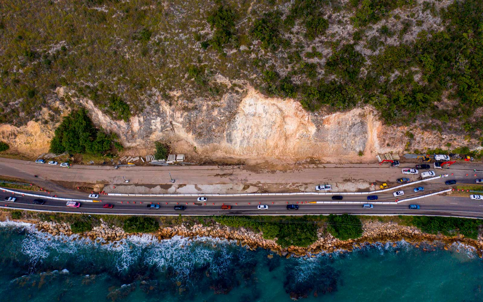 Cars drive through an area on highway 2 that was heavily affected by a landslide after after a powerful earthquake hit the island in Ponce, Puerto Rico on January 12, 2020.