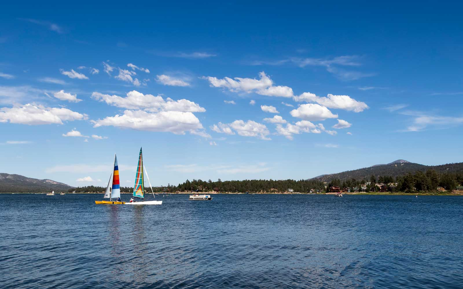Two Catamarans Sailing On Big Bear Lake Southern California With White Clouds In Blue Sky