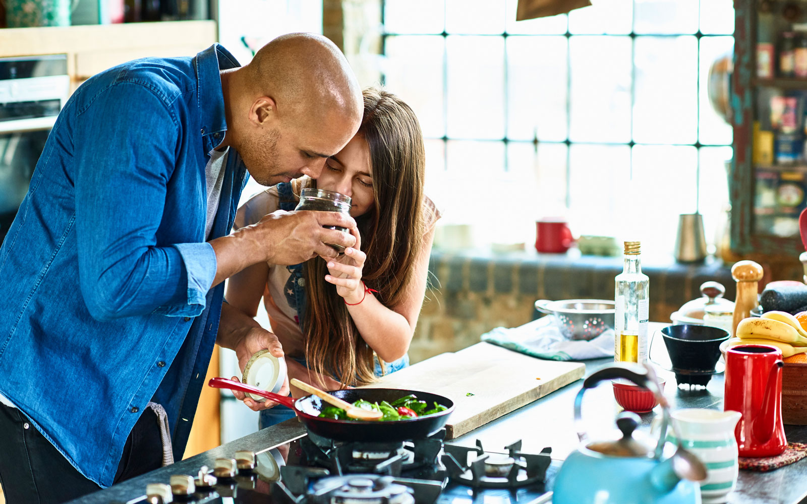 Father and daughter smelling spices while cooking in kitchen