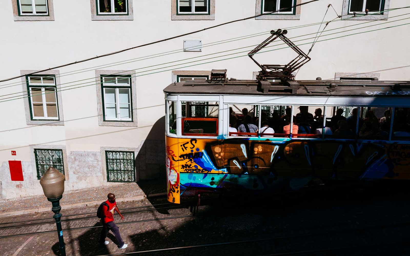 Man walking by a graffiti painted tram on cobbled street in Lisbon, Portugal