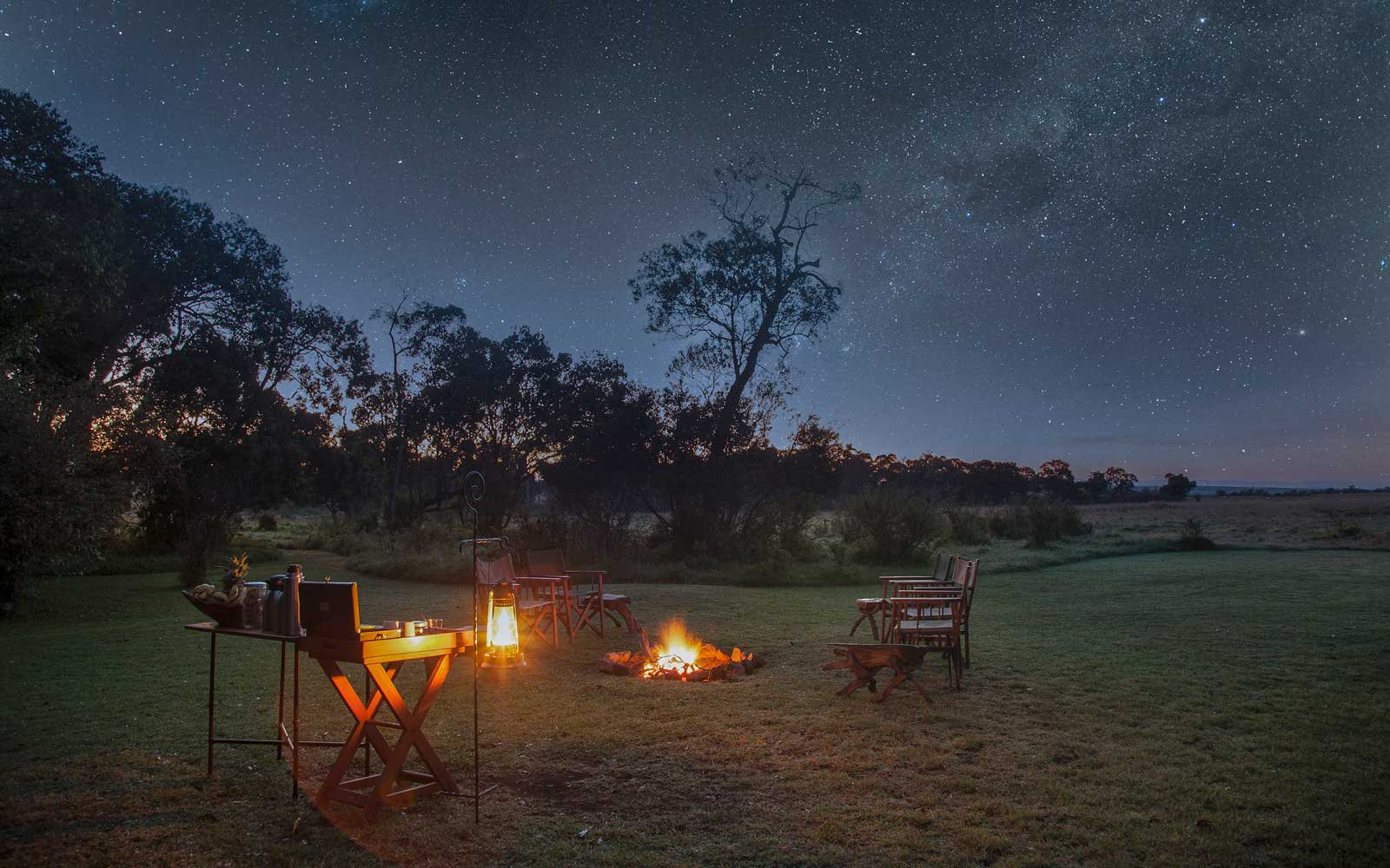 A safari camp at night under starry sky
