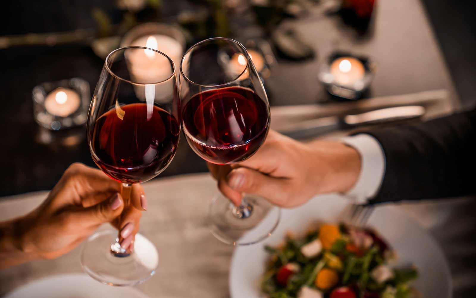 Close up of couple toasting with glasses of red wine at restaurant