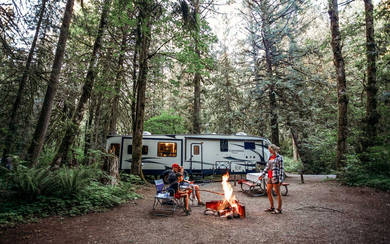 Family around fire, camping in an RV