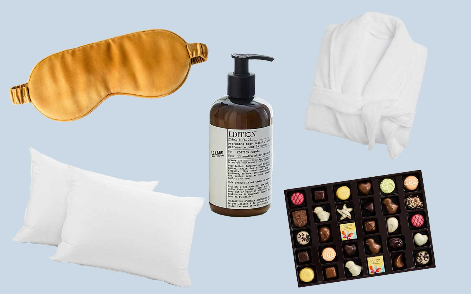 Gold sleep mask, white pillows, white robe, assorted chocolate box, and soap bottle with pump on blue background