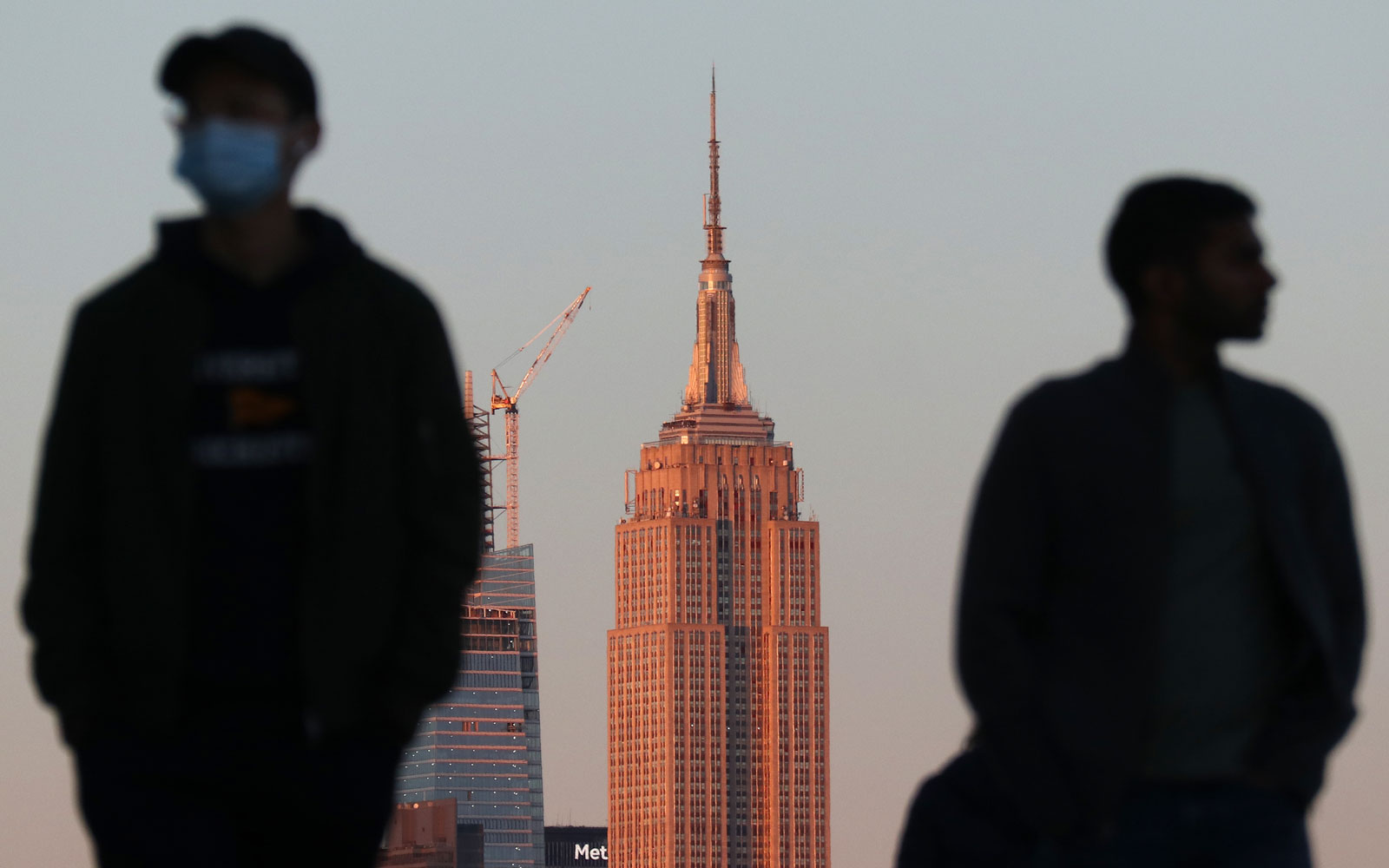 2 people stand in front of the empire state building