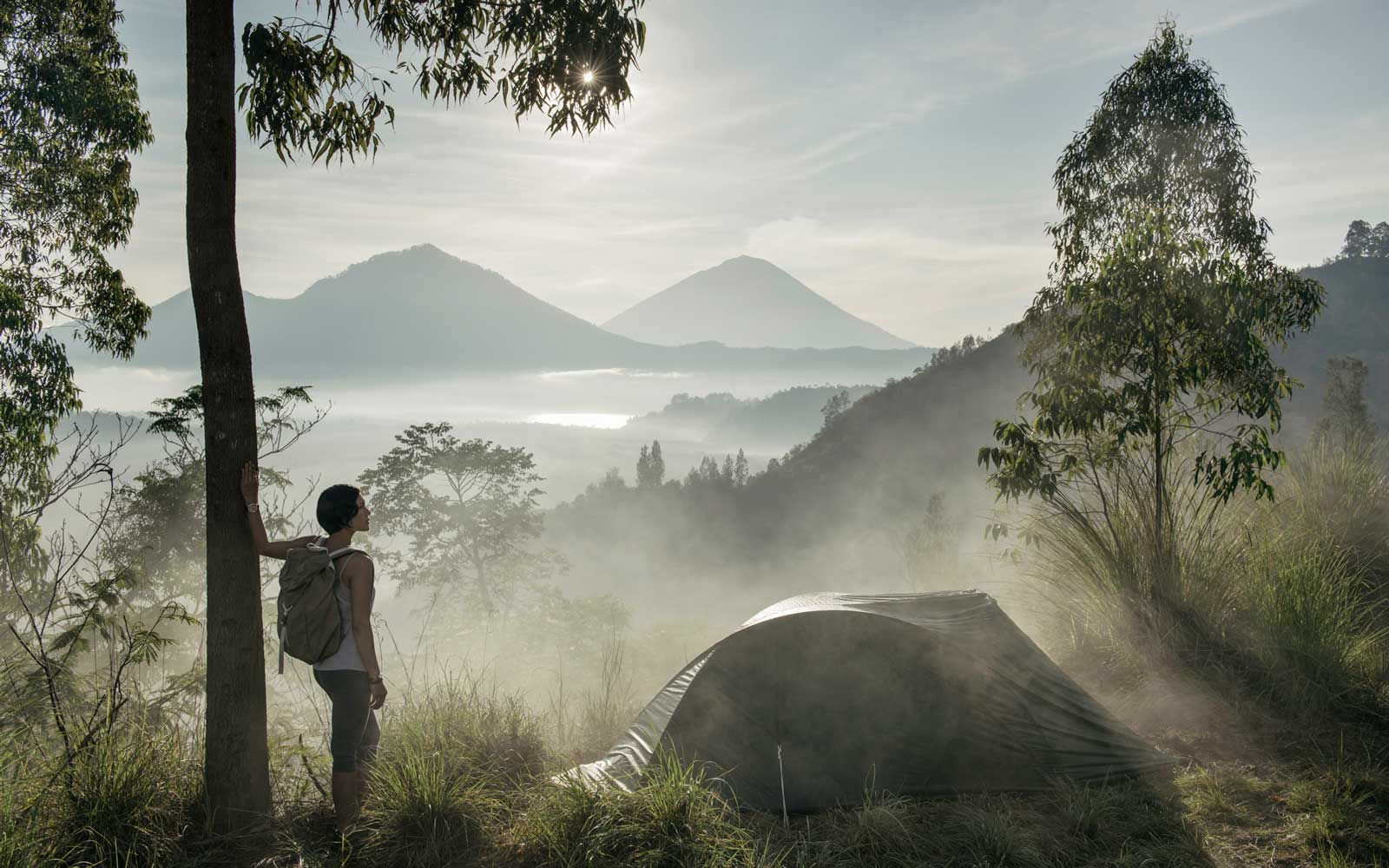 looking at the view while camping on Kintamani ridge, in front of Mount Agung volcano, at sunrise in Bali