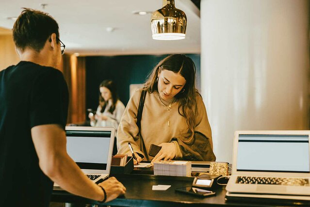 Man looking at woman signing at reception desk in hotel lobby