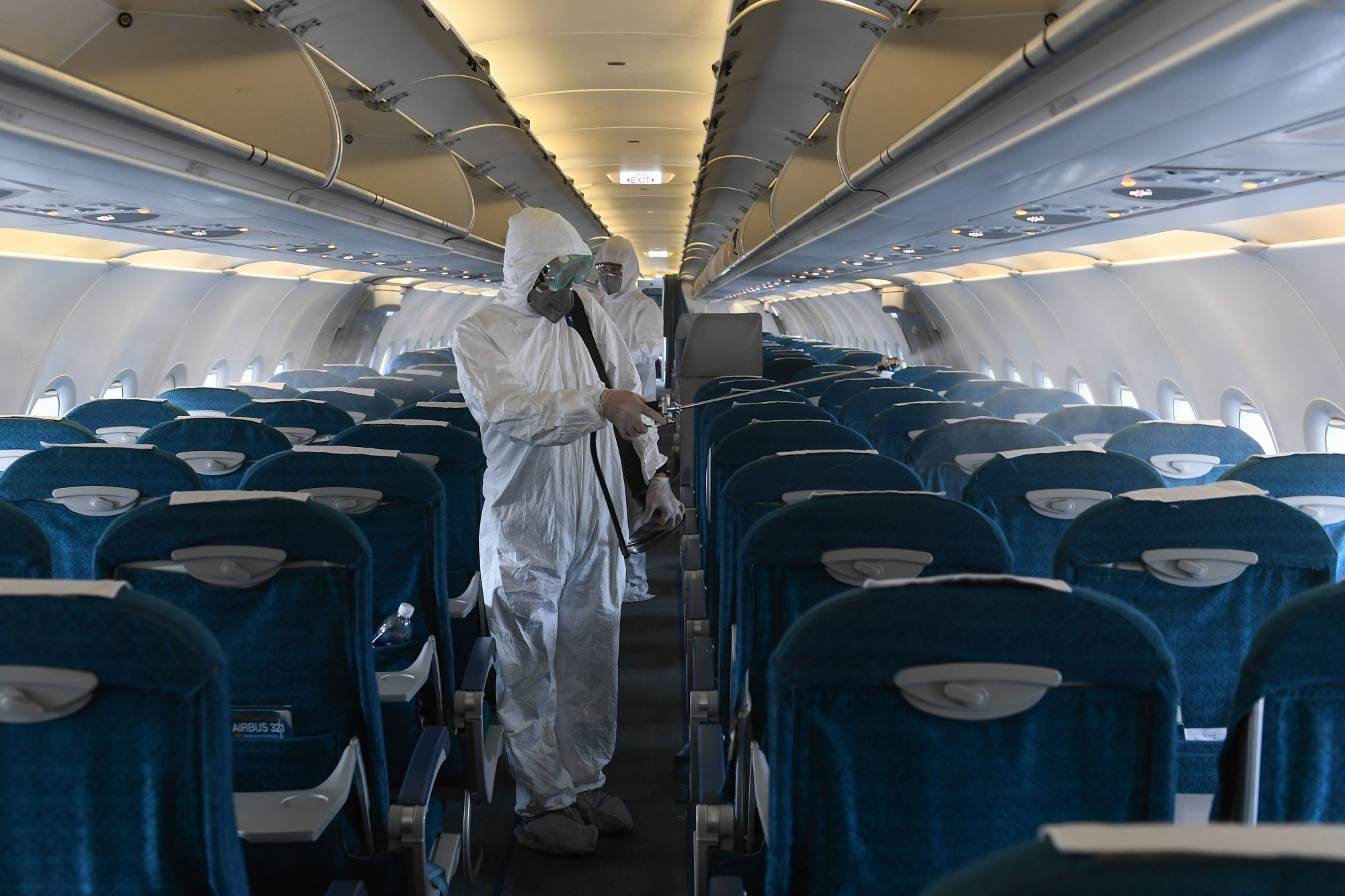 Workers wearing protective suits disinfect a Vietnam Airlines plane