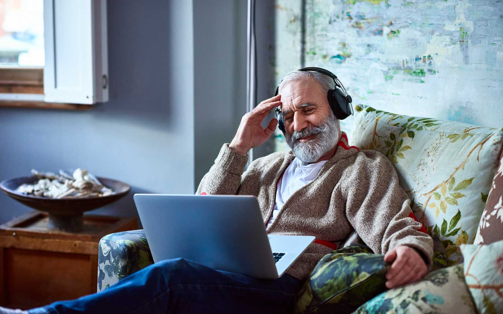 Cheerful man in his 50s watching a film on computer, smiling, sitting on comfortable sofa chair