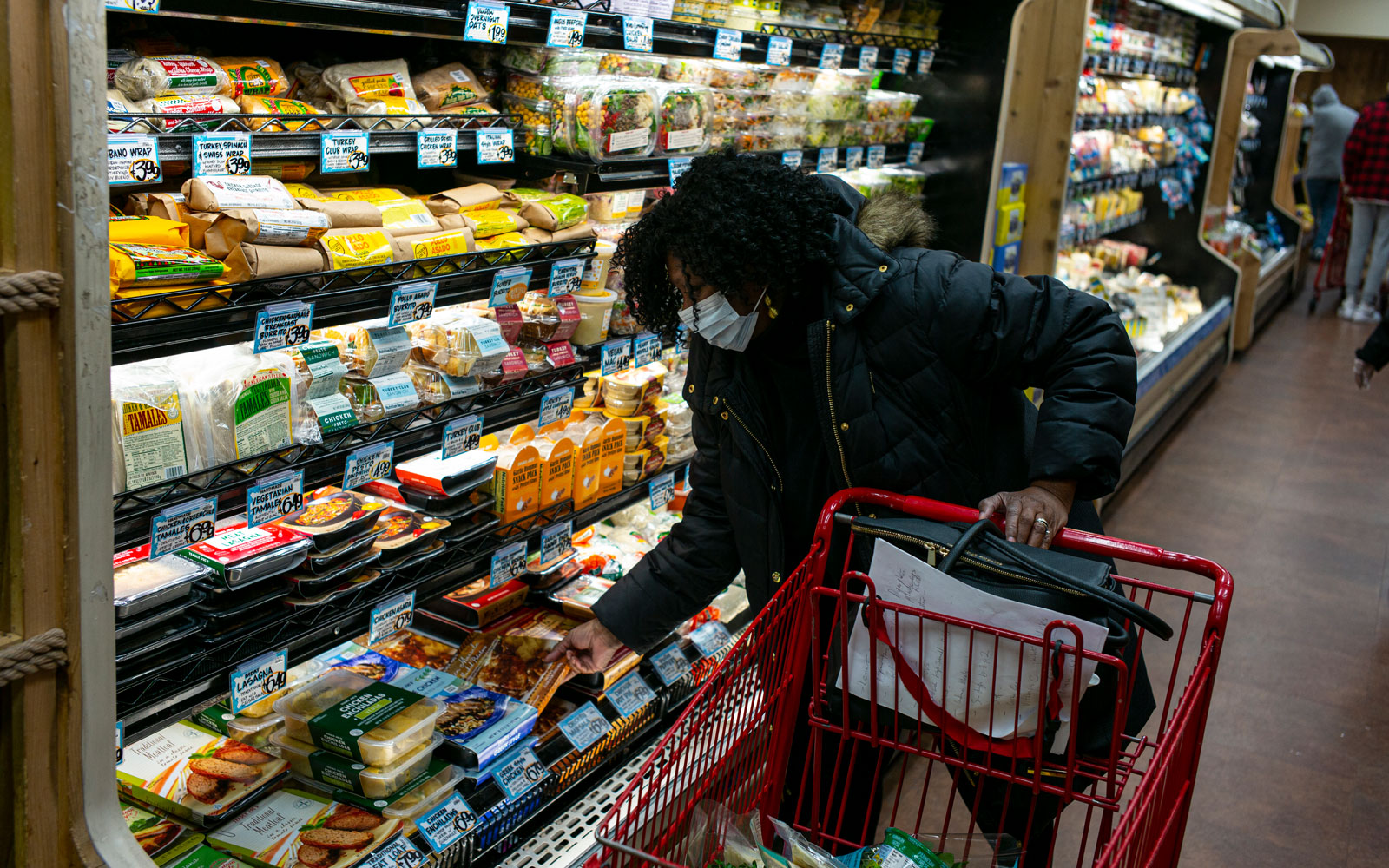 shopper wearing a surgical mask looks at a prepared meal at a Trader Joes