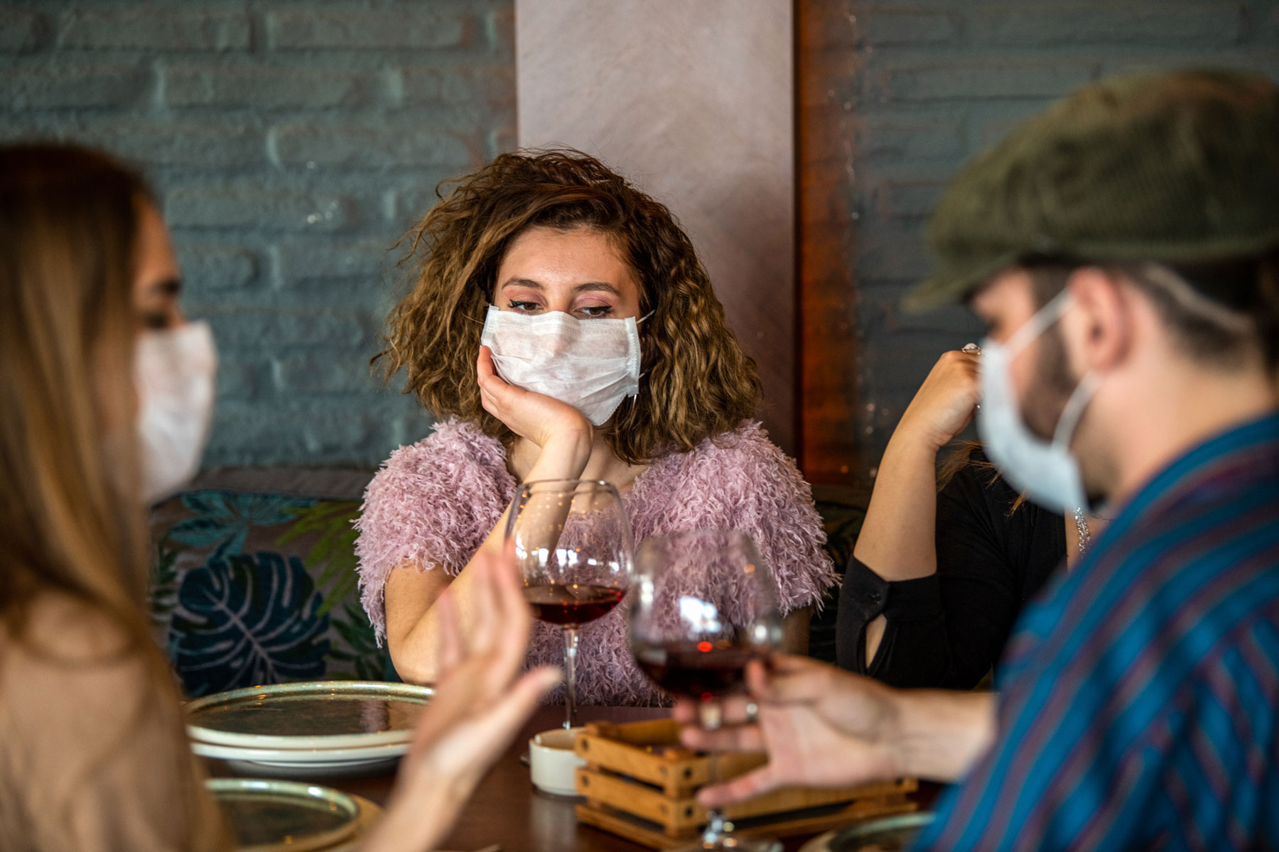 diners wearing face masks and holding wine glasses