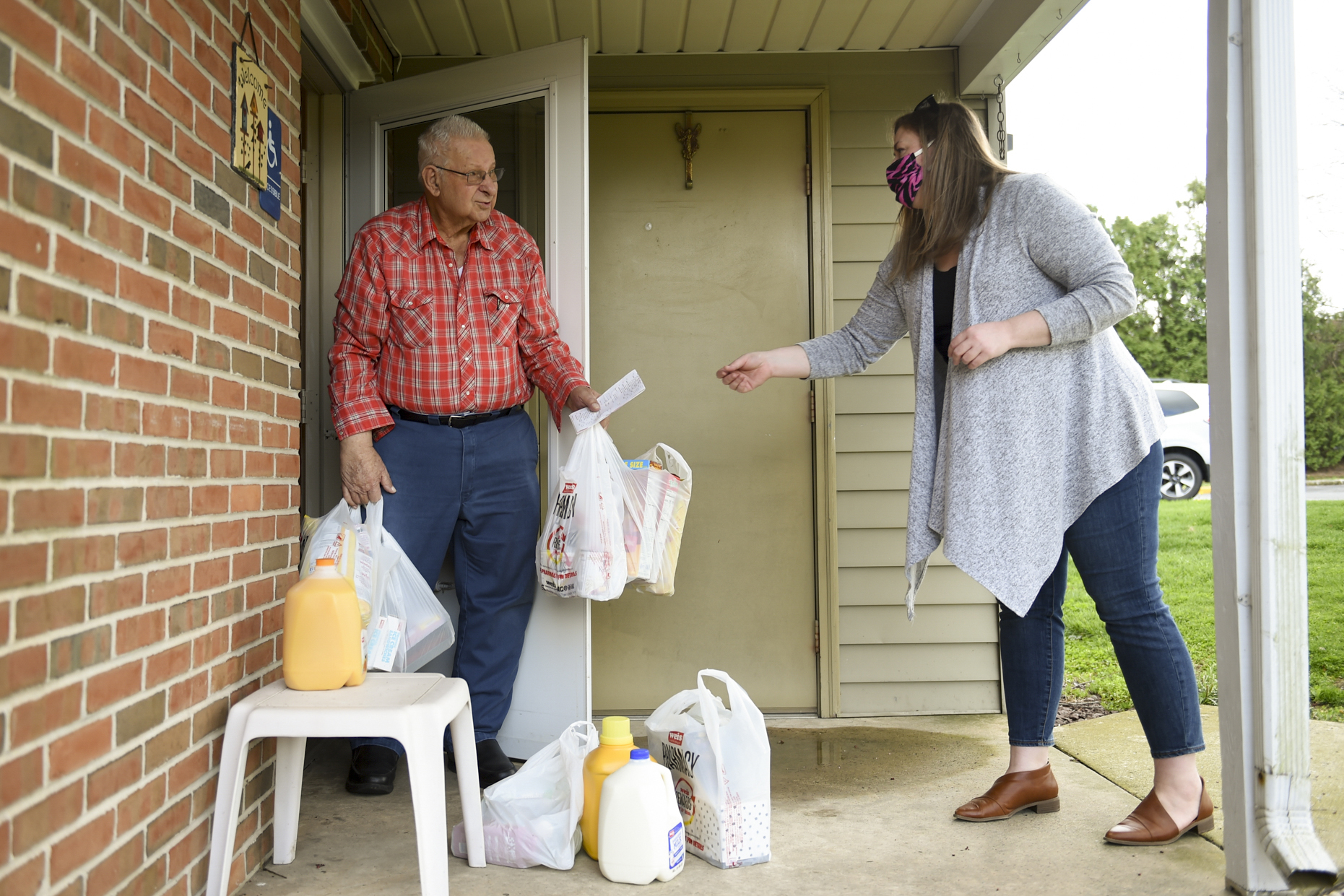 A woman delivers groceries to an elderly man.
