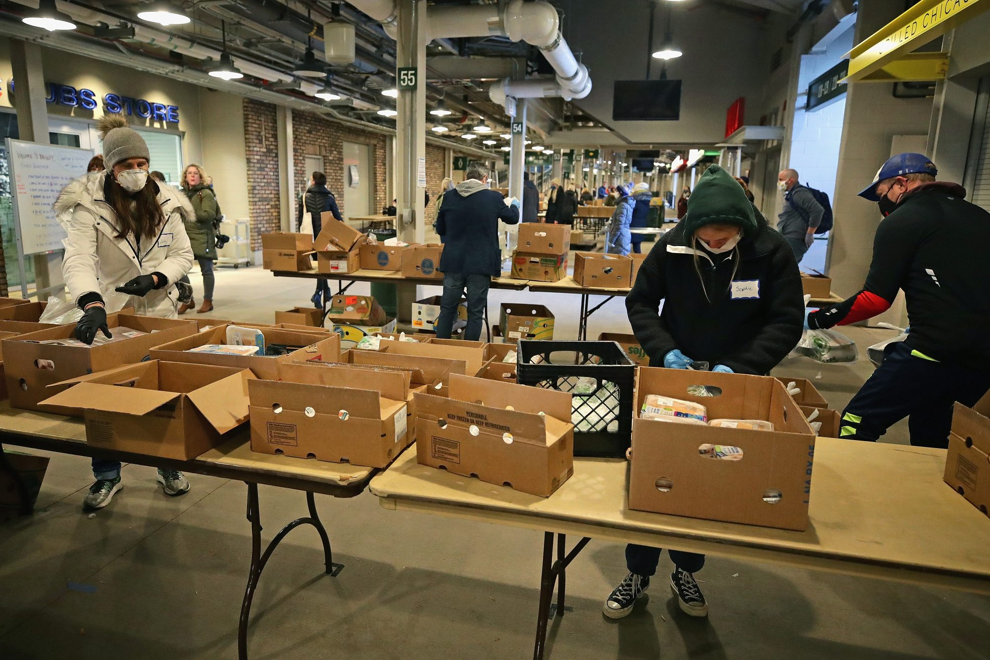 Volunteers fill cartons with food on the concourse of Wrigley Field.
