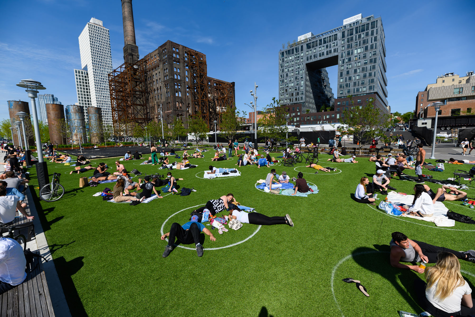 people sit in circles painted on the grass in Domino Park, Williamsburg