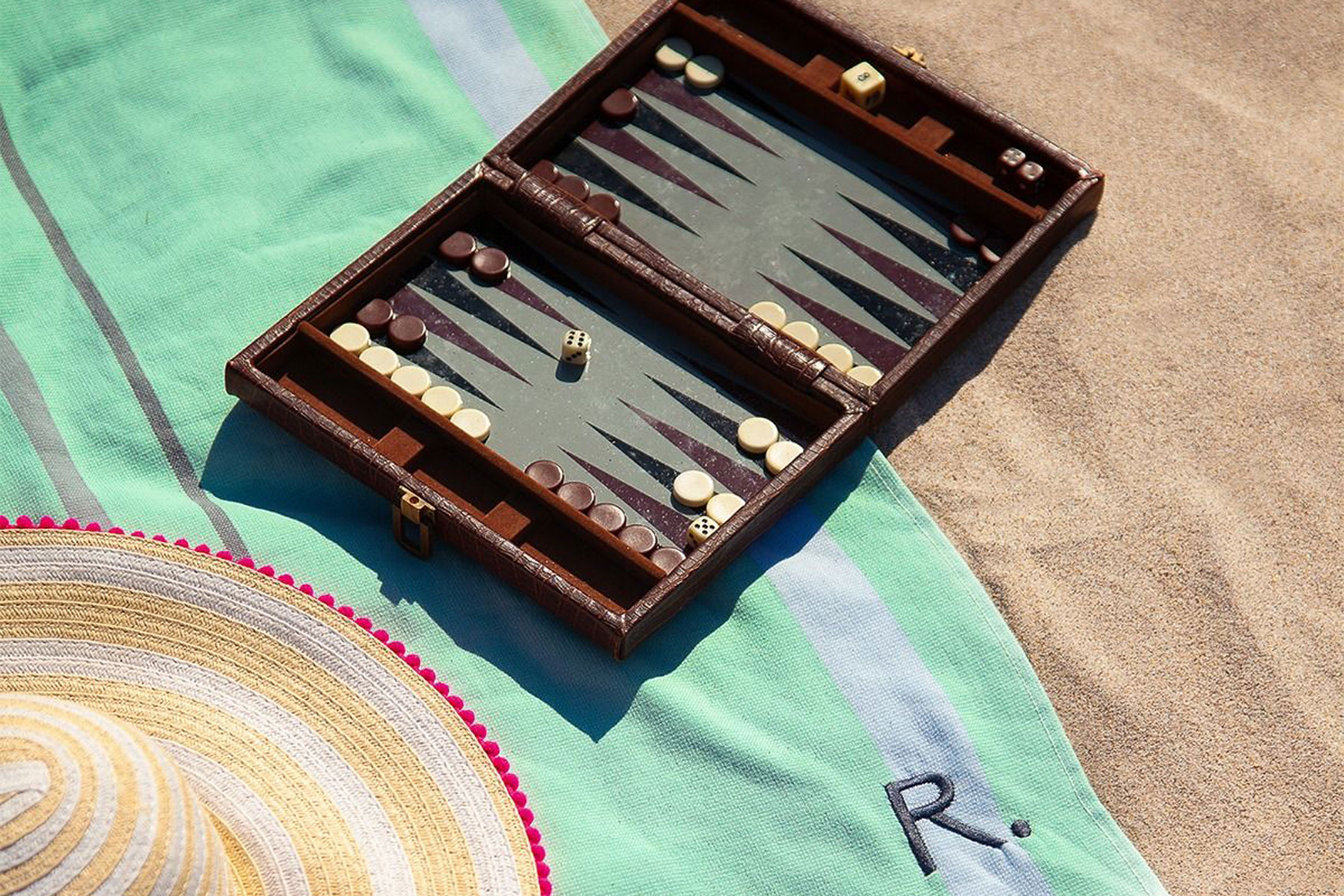 Green beach towel on sand with backgammon board