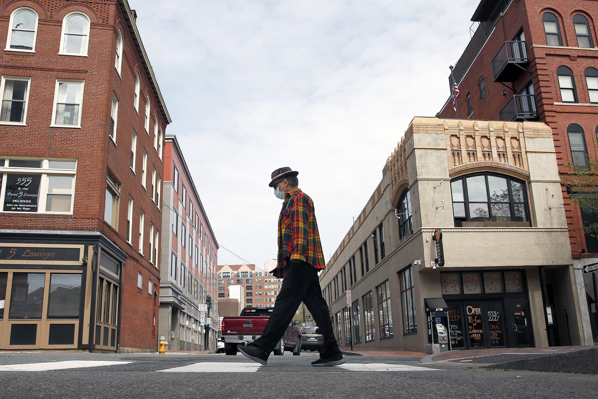 A man wears a mask while crossing Oak Street in Portland
