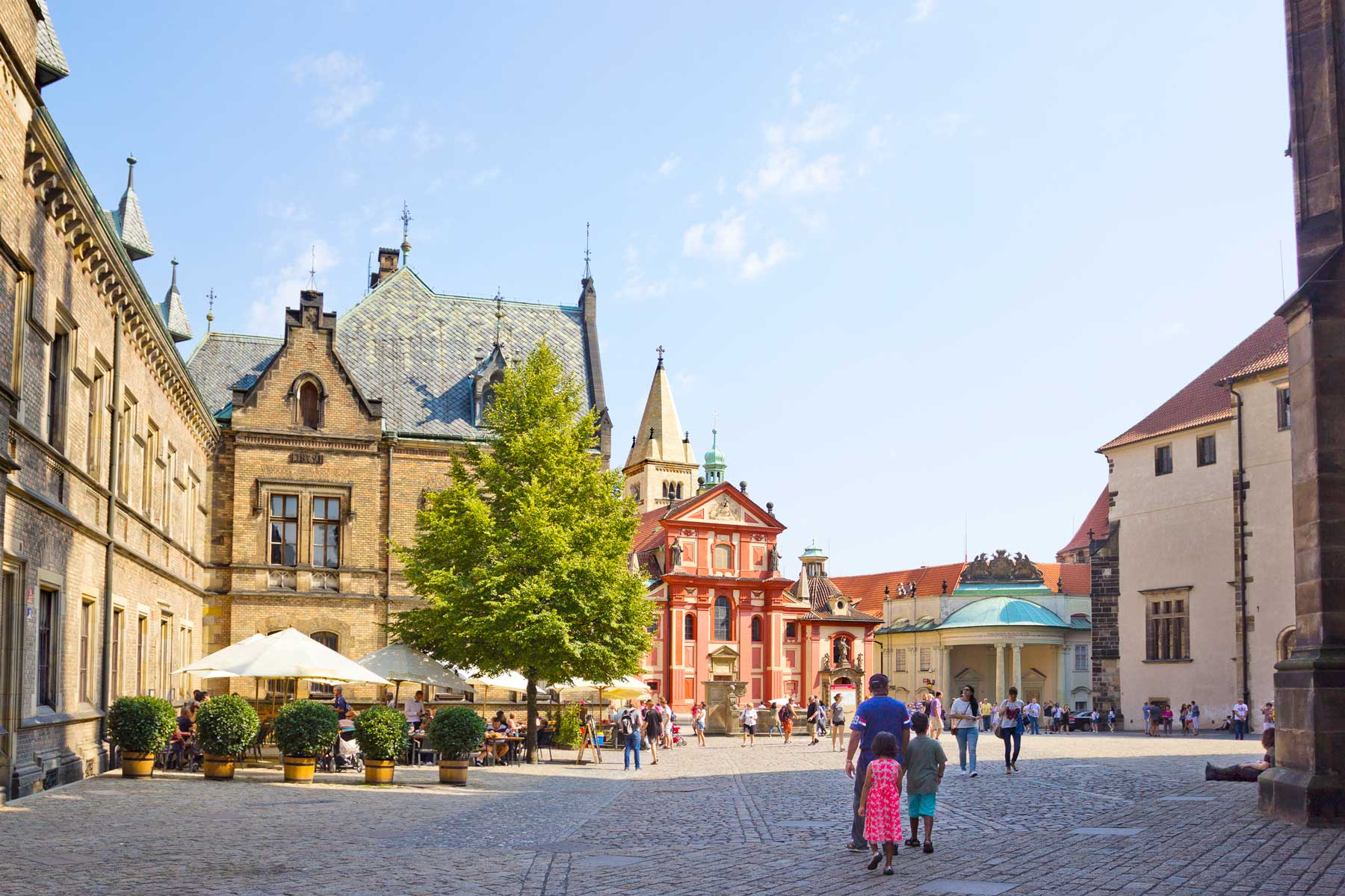 People sightseeing in the yard of Prague Castle, which is official residence of the President of the Czech Republic
