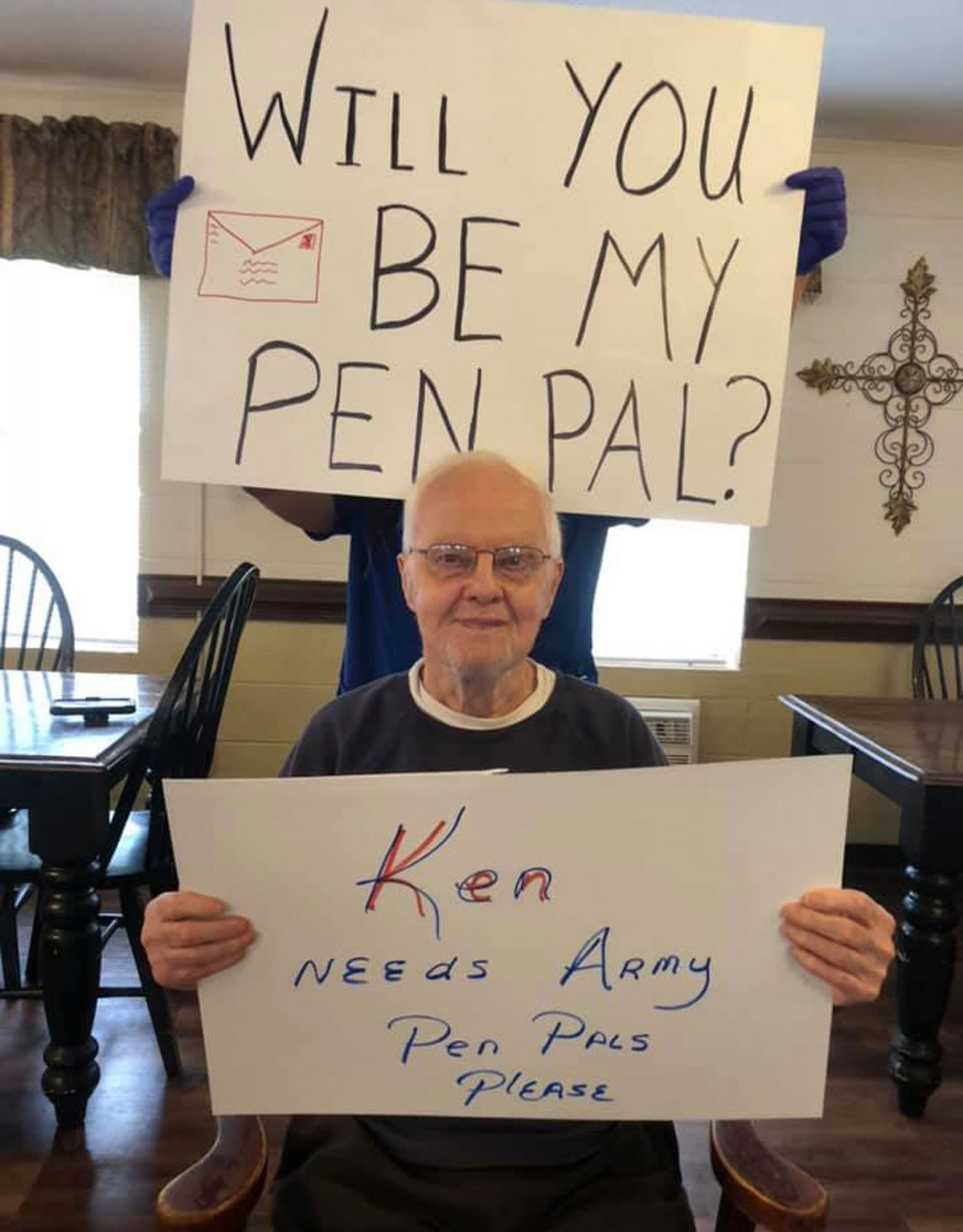 man holds white poster board that says Ken needs army pen pals