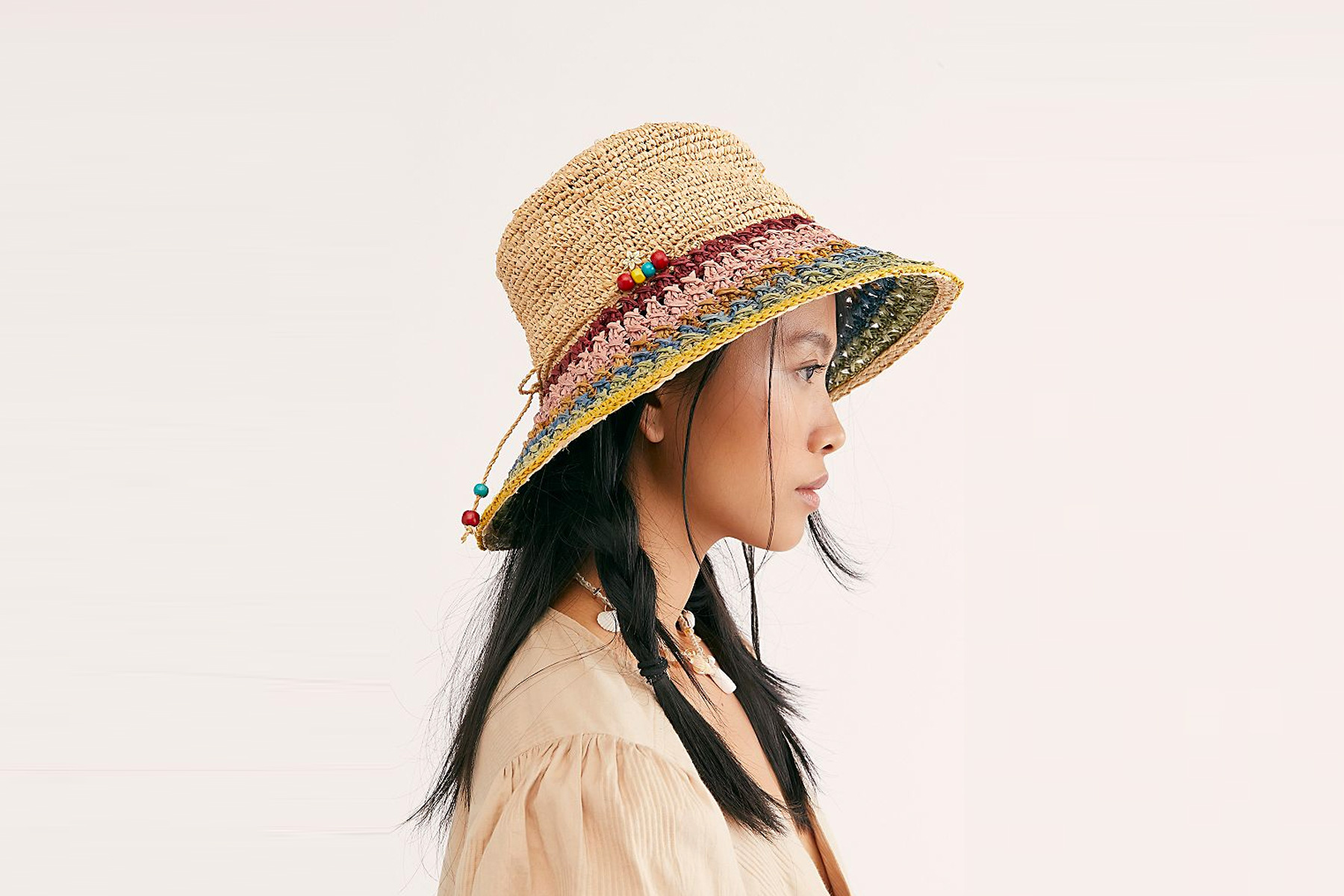 Woman wearing multi-colored woven straw hat