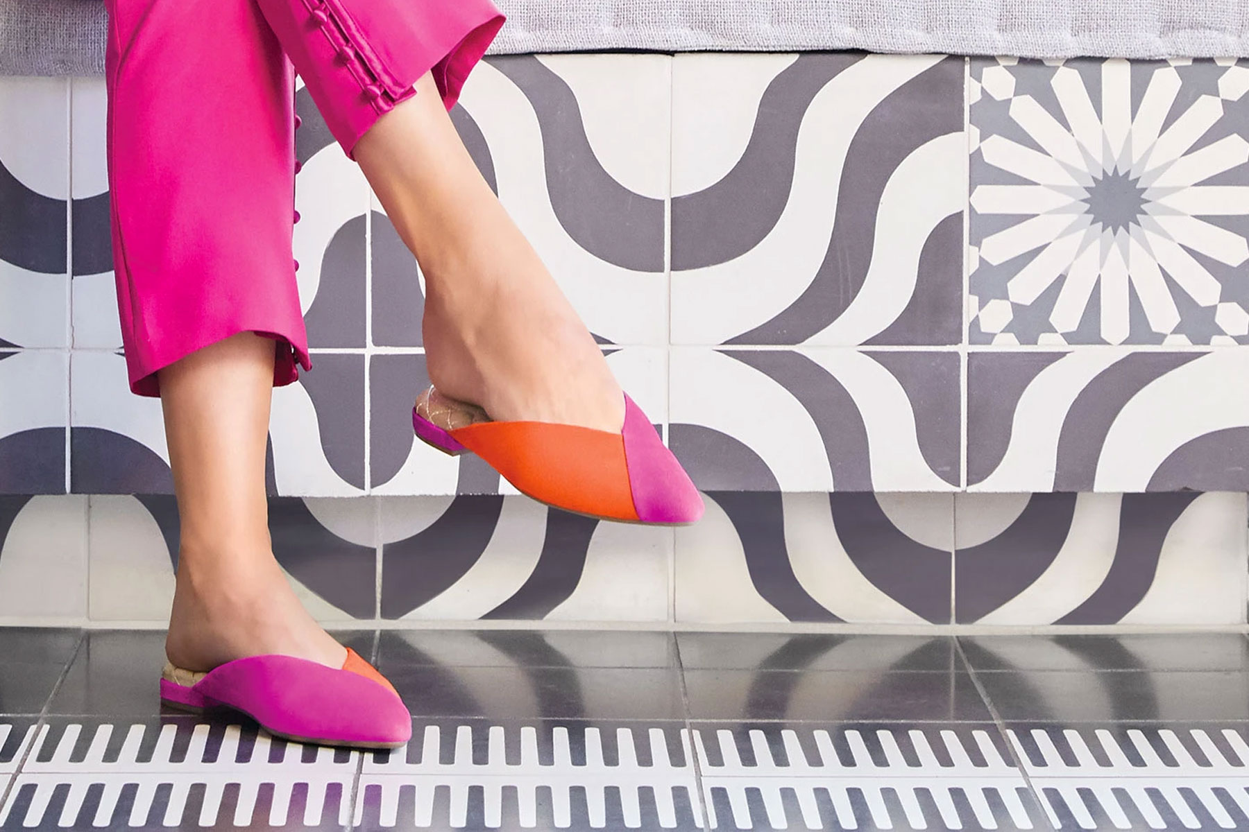 Woman wearing pink and orange slip on flats