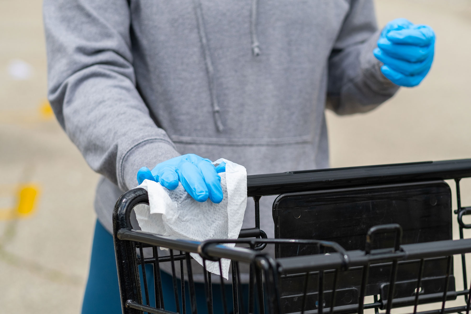 supermarket customer wiping a shopping cart