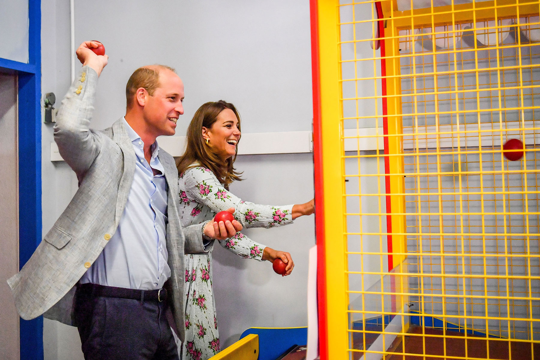 Prince William and Kate Middleton throw balls while playing an arcade game
