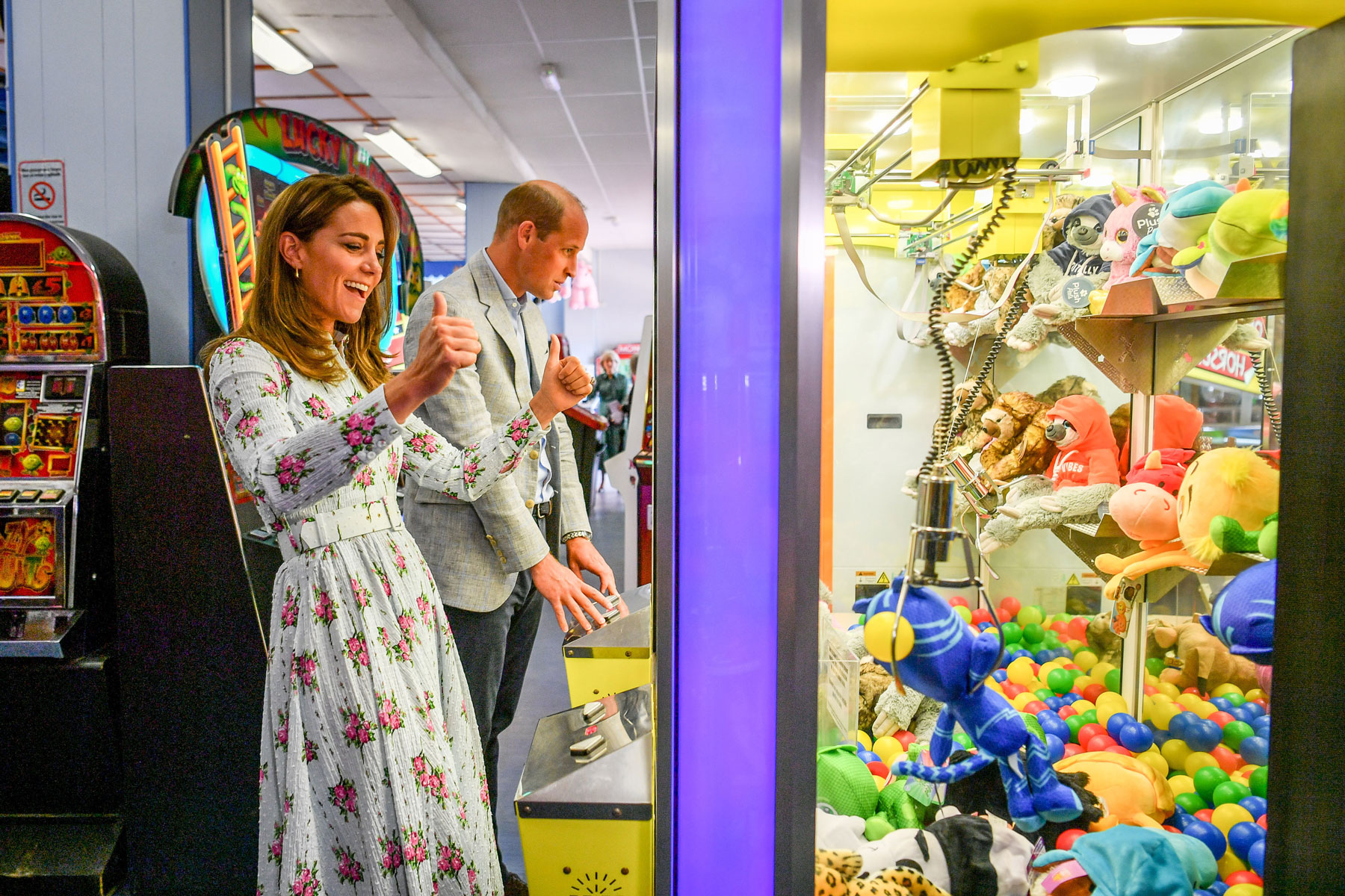 Kate Middleton cheers while operating an arcade claw machine