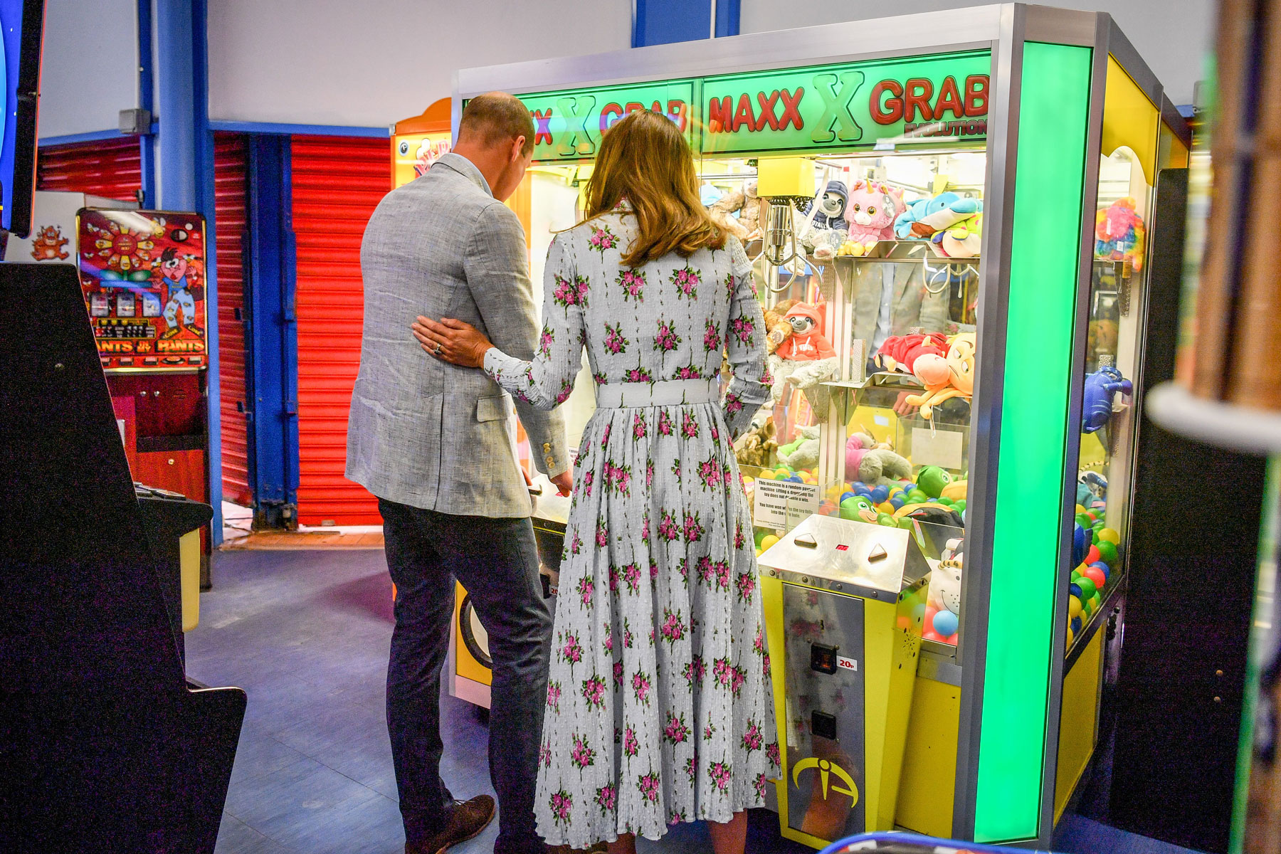 Prince William and Kate Middleton stand in front of an arcade claw machine