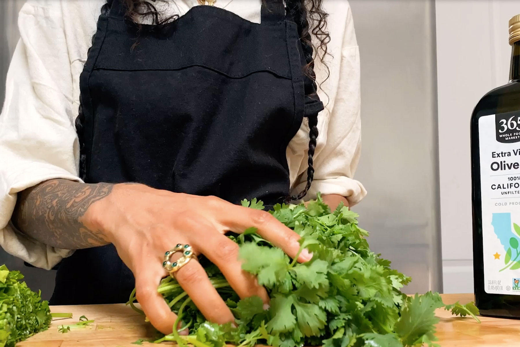 a chef holds herbs on a chopping board
