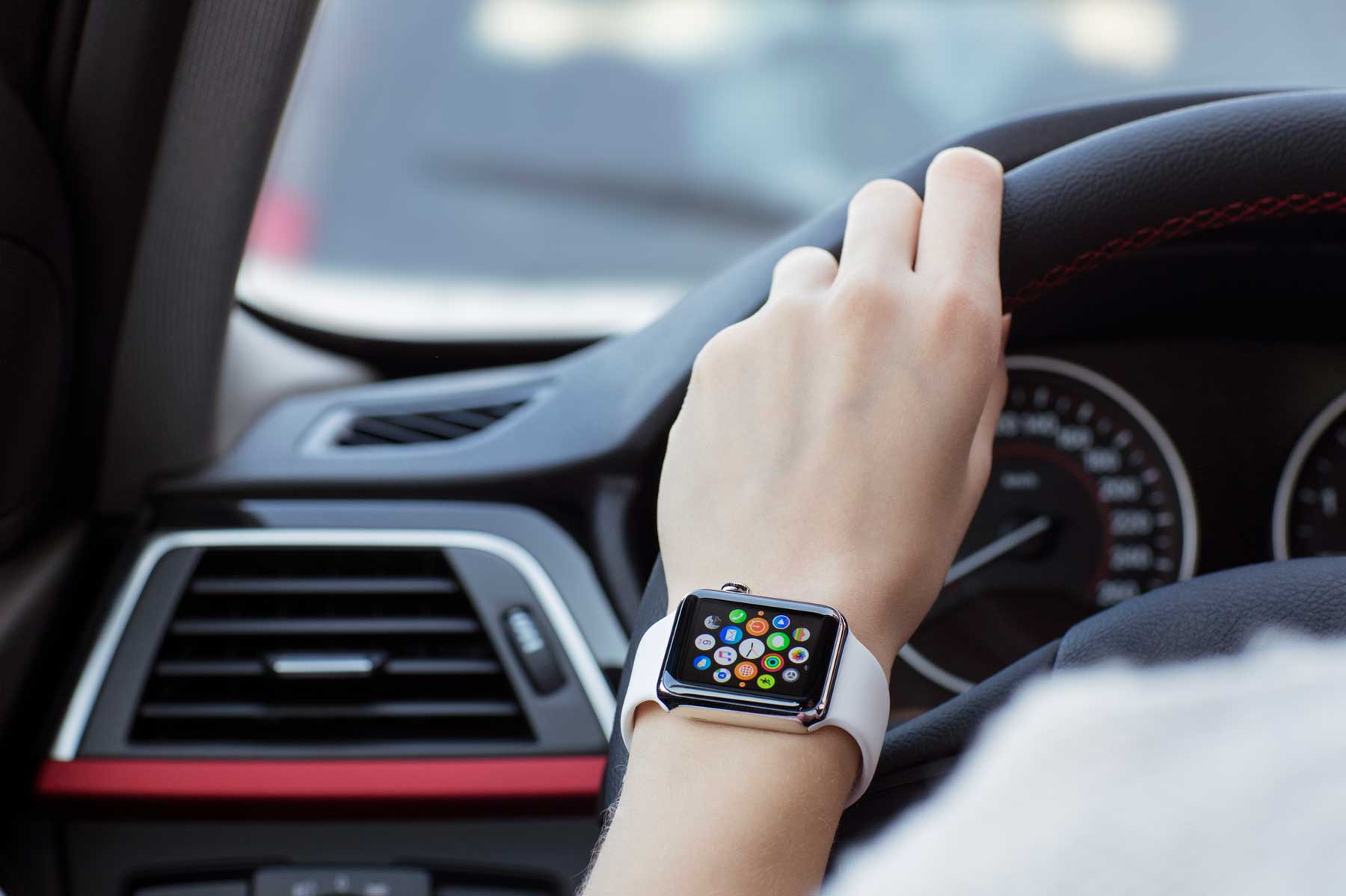 A woman wearing 38mm stainless steel Apple Watch in the car.