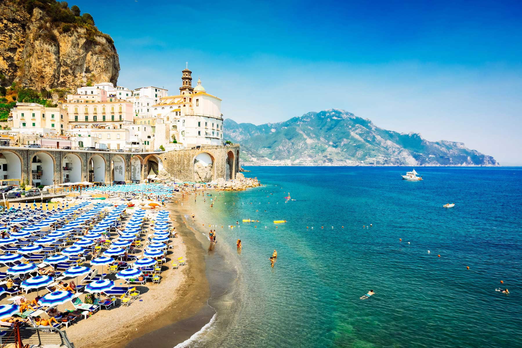 The Amalfi Coast in Italy with bright blue waters and the beach dotted with blue umbrellas.