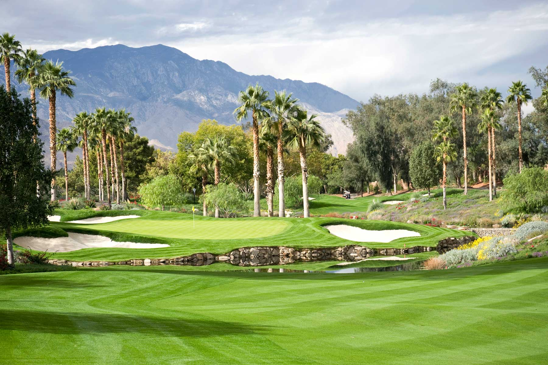 Golf course with palm trees and mountains in the distance